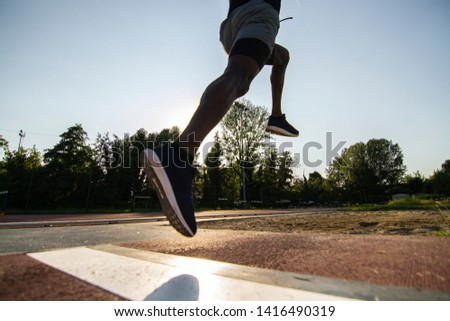 Close up of an young african male athlete is performing a long jump on race track in athletics stadium in a sunny day.
