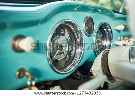 Close up of analog speedometer on dashboard with classic gauge and steering column. Classic car with pastel green interior. Car detailing & restoration of vintage concept. Selective foucs.