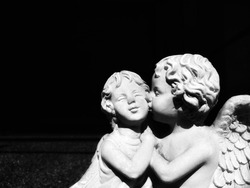 Close up of 2 angels in love moment with black background