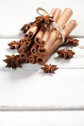 Close up of anise stars and cinnamon sticks on old wooden table. At the bottom is empty space to put text or something else. This file is cleaned and retouched.