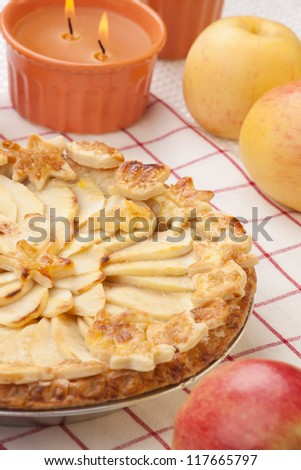 Close up of apple pie, ripe apples, and candles.
