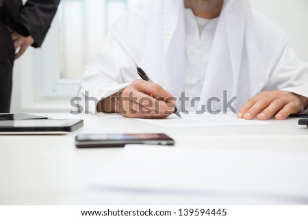 Close up of Arab businessman signing the contract. Focus is on hand