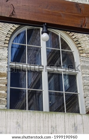 Close up of arch window with the wooden brown balk. Modern bulb in the center of the balk. Detailed view of the window of an old building. Architectural element. Rotermann city, Tallinn, Estonia Stockfoto ©
