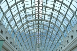 close up of arched glass domed steel structured window roof creating semi circle patterns letting daylight into building, looking through glass to blue sky and clouds