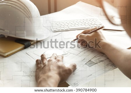 Close up of Architect sketching a construction project at work place vintage tone.Double exposure of blueprint.
