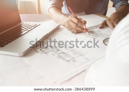 Close up of Architect sketching a construction project with laptop at work place. #386438899