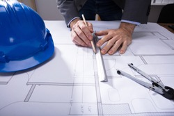 Close-up Of Architecture's Hand Working On Blueprint With Hardhat On Desk