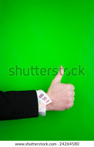 Close up of arm of businessperson giving thumbs up sign with bank notes tucked into suit sleeve, green background.