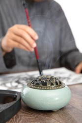 Close up of aromatherapy stove and calligraphers practicing calligraphy