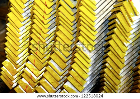Close-up of arrangement yellow steel angles bunch in warehouse