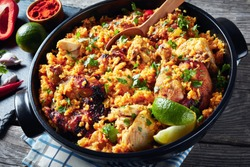 close-up of Arroz con pollo, spanish cuisine, rice with chicken and veggies in a black saucepan on a wooden rustic  table with ingredients on a slate board, view from above