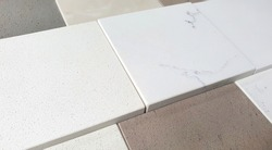 close up of artificial stone samples palette containing multi textures and colors. white, beige, grey quartz stone with grainy texture (focused at center of image).