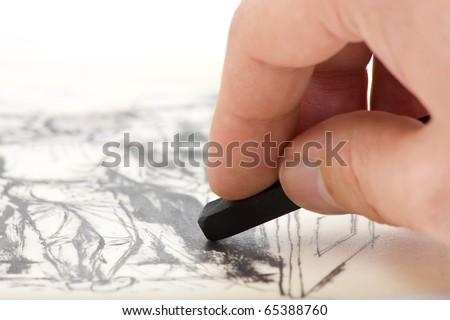 Close up of artists hand painting with graphite crayon