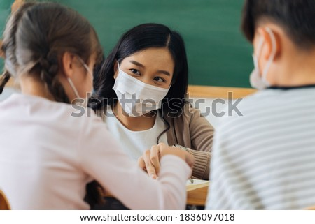 Close-up of Asian female teacher wearing a face mask in school building tutoring a primary student children. Elementary pupils writing and learning in classroom. Covid-19 school reopen concept