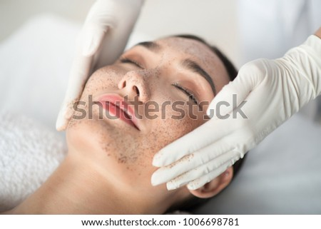 Close up of asian girl enjoying skin care treatment. Beautician hands pampering her face with scrub #1006698781