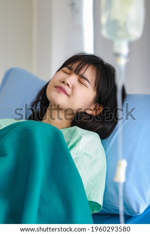 Close-up of asian sick female patient covered with a blanket lying on hospital bed having intravenous drip saline solution, feeling ailing and suffering from her illness Foto stock ©