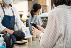 Close up of Asian woman customer make a quick and easy contactless payment in cafe during Covid19 Pandemic. Young girl use smartphone Scanning QR code to pay for service and drink from barista waiter.