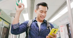 close up of asian young man use 5g smartphone on the mrt or train