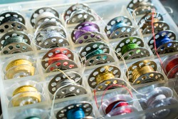 Close-up of assorted plastic and stainless steel bobbins or spools of sewing thread of different colors and kinds of thread, neatly organised in a plastic container.
