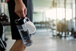 Close-up of athletic man carrying face mask and bottle of water while entering gym during coronavirus epidemic.