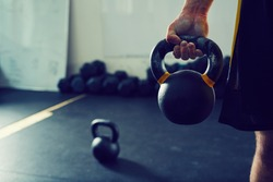 Close-up of athletic man holding kettlebell weight at gym