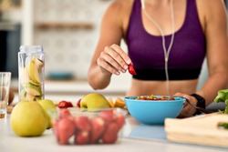 Close-up of athletic woman adding strawberries while making fruit salad in the kitchen.