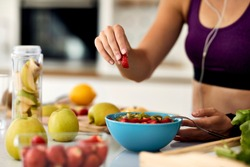 Close-up of athletic woman eating healthy and preparing fruit salad in the kitchen.