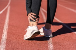 Close up of athletic woman runner touching foot in pain due to sprained ankle, rear view. Running sport, injury from workout