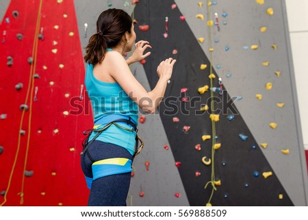 Close up of athletic woman standing in a bouldering gym and preparing for climb #569888509