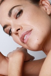 Close-up of attractive middle aged woman touching her cheek skin, mature beauty concept. Skin imperfections.