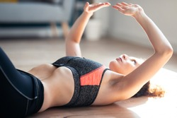 Close up of attractive sporty young woman doing hypopressive exercises in living room at home.