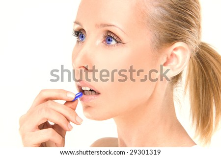 close up of attractive woman looking  taking a pill