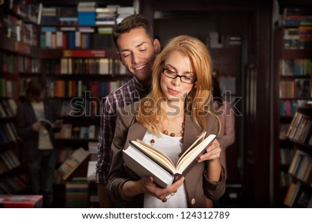 close-up of attractive young couple in a library reading a book together with other people and bookshelves in background
