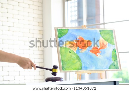Close up of auctioneer is holding  wooden auction hammer , make dicision while bidder offering highest price  in  goldfish painting art auction.