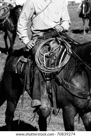 Close-up of authentic cowboy in the American West preparing to work inside an arena with other cowboys in the background (shallow depth of field, black and white).
