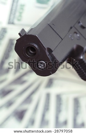 Close-up of automatic pistol on background with money