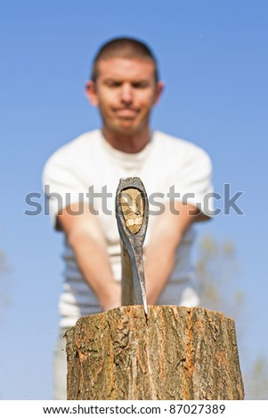 Close up of axe head splitting a log with a male figure with narrow depth of focus against a beautiful blue sky