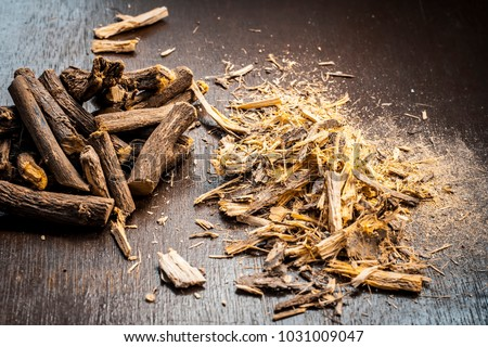 Close up of Ayurvedic herb Liquorice root,Licorice root, Mulethi or Glycyrrhiza glabra root and its powder on a wooden surface is very much beneficial for Soothes your stomach,poisoning, stomach etc.