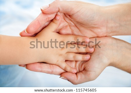 Close up of babies hand resting on mothers hand.