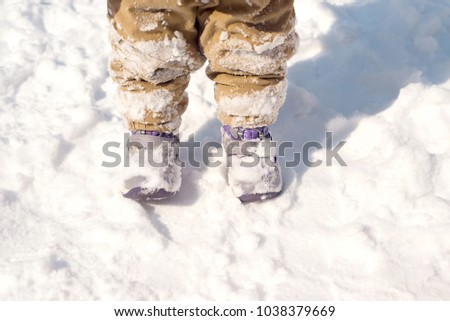 Close up of baby feet in winter boots covered with snow #1038379669