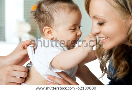 Close-up of baby girl being examined by doctor, playing with mother