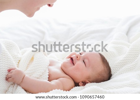 Close up of baby smiling at his mother. Newborn child looking up at mother . Love, cheerful, realtionships.