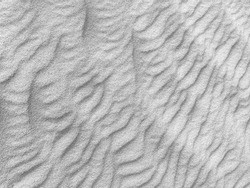Close up of background texture of desert sand dunes. Beautiful structures of sandy dunes on sunny summer day. Annual growth of area of sand with wave from wind in desert for holiday vacation concept