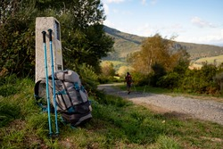 Close up of backpack with walking stick and Camino de Santiago sign, with pilgrim walking along the path, symbol of pilgrimage and walking on the way to Santiago