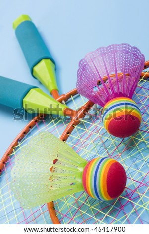 Close-up of badminton rackets and balls on a blue background