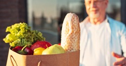 Close up of baguette and fresh vegetables in packet. Courier bringing food to old Caucasian man and handing outdoor. Deliveryman bringing grocery to male pensioner.