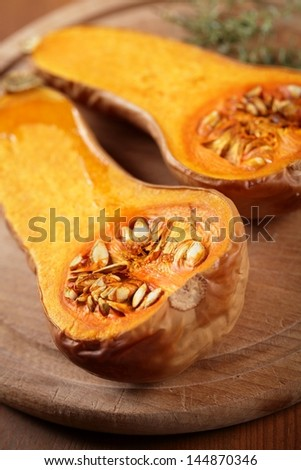 Close up of baked butternut squash and herbs on wooden board.