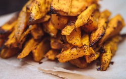 Close up of baked or roasted sweet potato fries on a baking paper. Side view, close up of fried sweet potato.