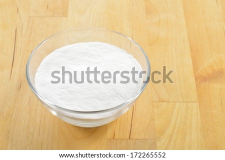 Close-up of baking soda in a glass bowl against background of wooden table. Bicarbonate of soda.