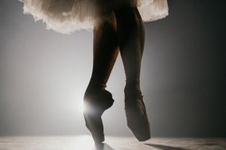 Close up of ballet dancer as she practices exercises on dark stage or studio. Woman's feet in pointe shoes. Ballerina shows classic ballet pas. Slow motion. Flare shot.